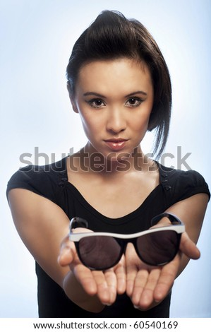 Young woman holding sunglasses - stock photo