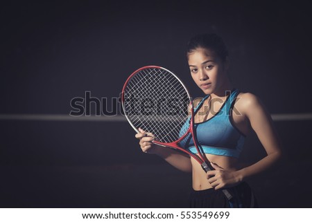 Young woman holding tennis racket on black.