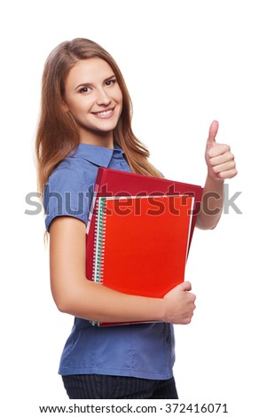Young woman holding textbooks smiling at camera and gesturing thumb up, over white background - stock photo