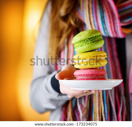 Young woman holding the french pastry macaron in cafe.