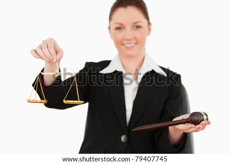 Young woman holding the justice symbols against a white background - stock photo