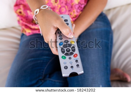 young woman holding the television remote control - stock photo