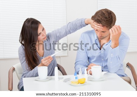 Young woman holding thermometer while looking at ill man in house - stock photo