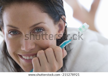 Young woman holding toothbrush, smiling, portrait, close-up