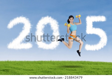 Young woman holding two dumbbells, jumping on field and forming number 2015 with cloud