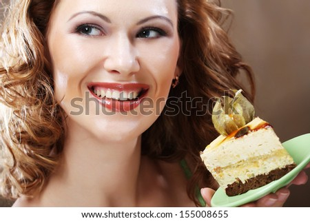 young woman holding up a delicious piece of cake - stock photo