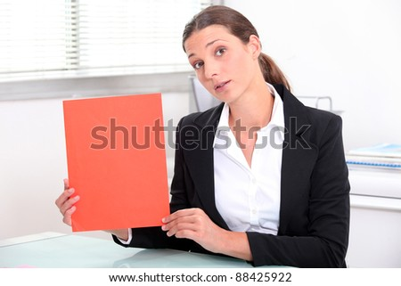 Young woman holding up a red file - stock photo