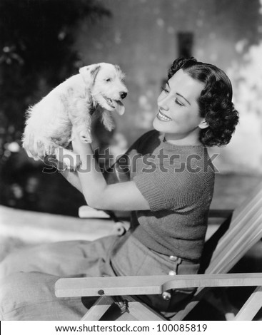 Young woman holding up her puppy and smiling - stock photo
