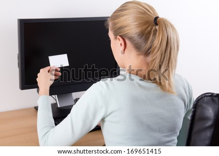 young woman holding visiting card and using pc with copy space on screen - stock photo