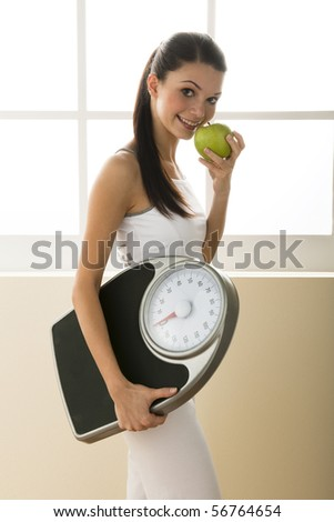 Young woman holding weight scale - stock photo