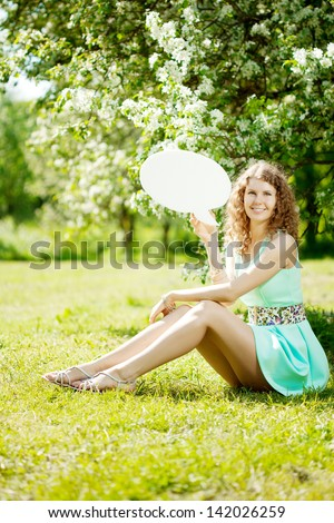 Young woman holding white bubble talk in summer park