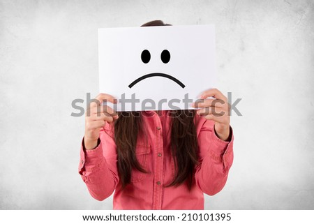 Young woman holding white card with sad face expression on grunge background.