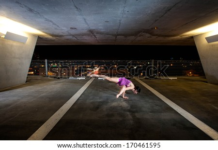 Young Woman holding yoga poses in a public space - stock photo