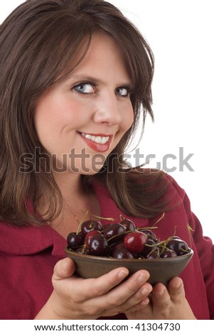 Young woman holds a bowl of cherries; isolated on a white background. - stock photo