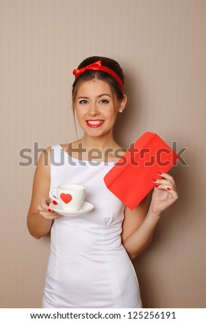Young woman holds a mail and a cup with a red heart