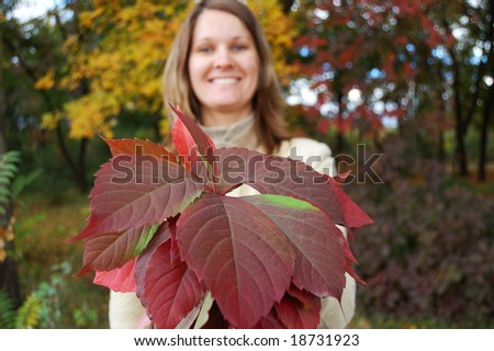 Young woman holds bouquet of autumnal leaves - stock photo
