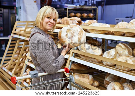 Young woman holds bread and smile - stock photo