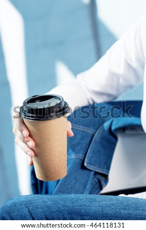 Young woman holds disposable brown paper cup of coffee. Copy space on cup. Positive and light mood
