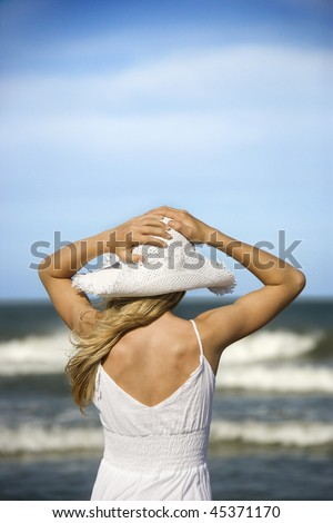 Young woman holds her hat down as she looks out at the ocean from the beach. Vertical shot. - stock photo