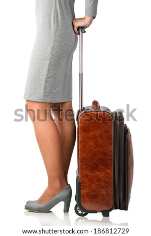 Young woman holds leather suitcase with copy space. Business trip concept - stock photo