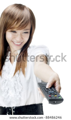 Young woman holds out a remote control to change television stations. - stock photo