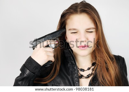 young woman holds pistol near the temple - stock photo