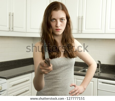 Young woman holds sharp knife in kitchen in an aggressive manner - stock photo