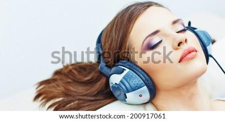 Young woman home portrait. Sleeping girl with headphones. Music. - stock photo