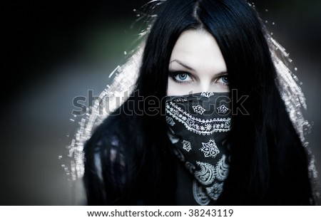 Young woman hooligan with scarf portrait. Dark dramatic colors. - stock photo
