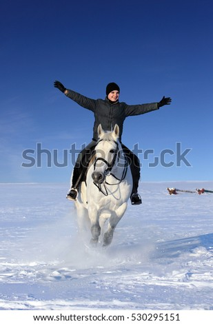 Young woman horseback riding gallop in the snow