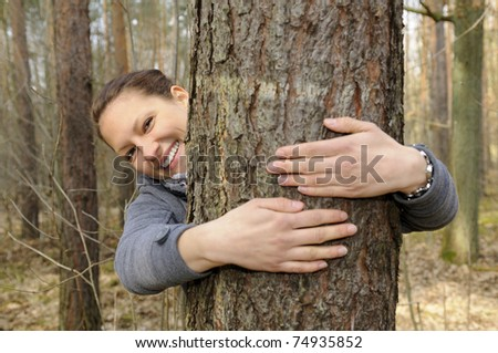 young woman hugging a tree - stock photo