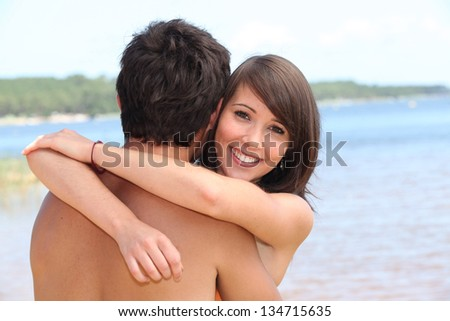 young woman hugging boyfriend at beach - stock photo