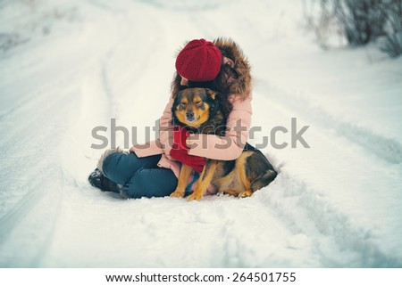 Young woman hugging dog on snowy road - stock photo