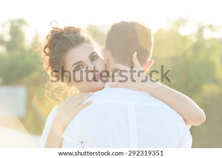 Young woman hugging her boyfriend. Back light and lens flare - stock photo