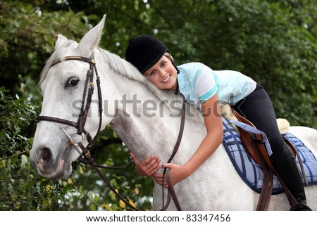 Young woman hugging her horse - stock photo