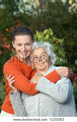 Young woman hugging her ninety year old grandmother - stock photo