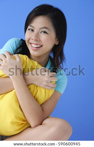 Young woman hugging pillow, portrait