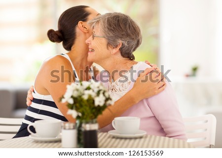 young woman hugging senior mother when visiting her - stock photo