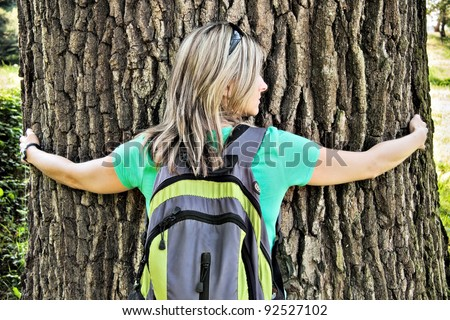 Young woman hugging the tree - stock photo