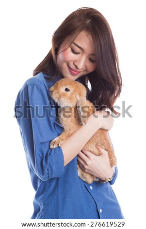 Young woman hugs cute golden rabbit in her arms on white background. Pet, loving Concepts.