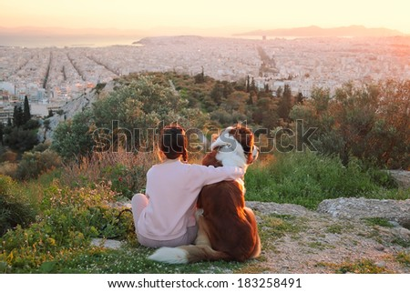 Young woman hugs her dog as they sit in a field.Athens,Greece.Real warm light from sunset. - stock photo