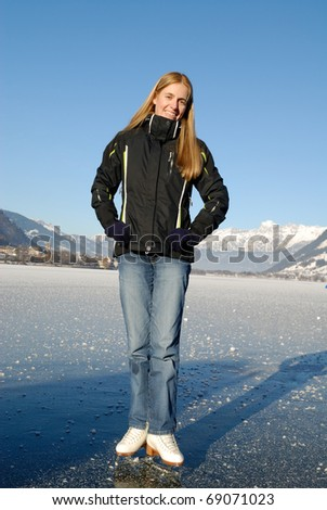 Young woman ice skating on frozen lake on a sunny day - stock photo