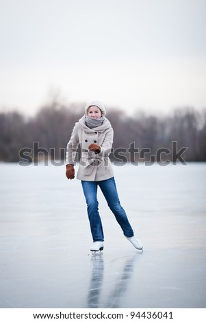 Young woman ice skating outdoors on a pond on a freezing winter day - stock photo