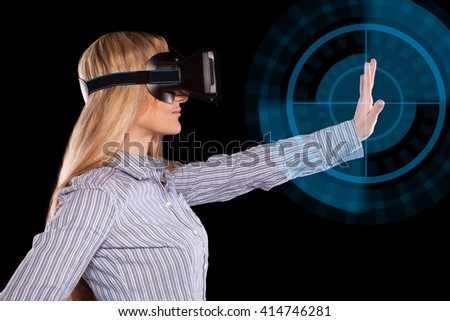Young woman immersed in interactive virtual reality video game doing gestures on black background.