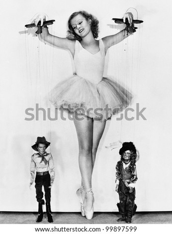 Young woman in a ballerina tutu keeps on her toes to control the men at her feet - stock photo