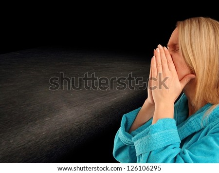 Young woman in a bath robe sneezing with back-light - stock photo