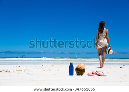 Young woman in a beautiful beach with coconut and sunblock in the foreground, Kenya, Africa.