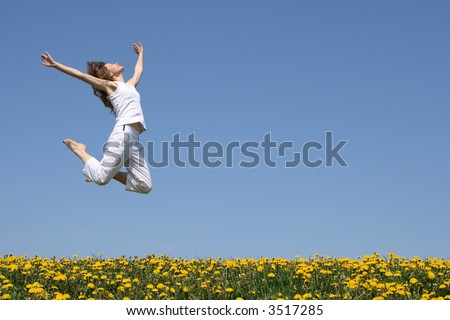 Young woman in a beautiful happy jump in flowering field. - stock photo