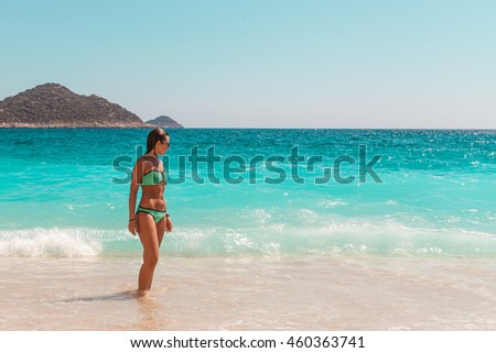 Young woman in a bikini bathing in the waves of the Mediterranean Sea, on Kaputas Beach, Turkey