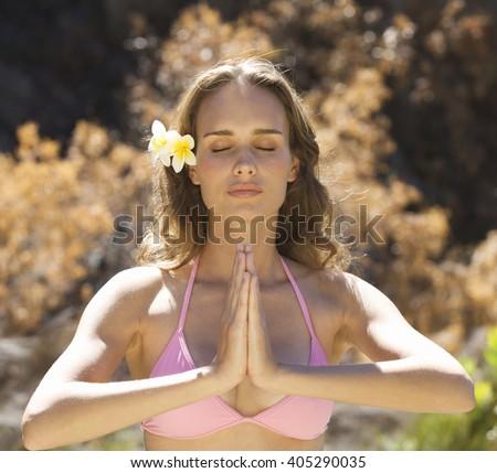 Young woman in a bikini practicing yoga - stock photo